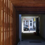 The passageway towards the parking featuring wood slats